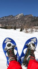 man with blue modern snowshoes in the mountain