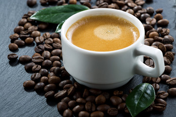cup of espresso on coffee beans background, selective focus