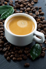 cup of espresso on coffee beans background, vertical, close-up