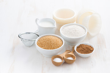 Ingredients for baking muffins on white wooden table