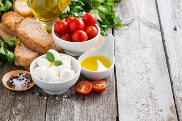 mozzarella and ingredients for the salad on a wooden background