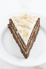 piece of chocolate cake with cream on a plate, vertical