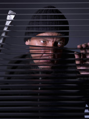 Thief spying across a blind