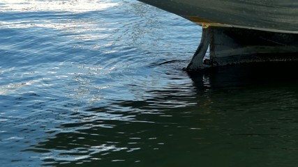 Rudder of the boat is in port, close-up. In slow motion.