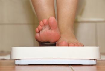 Feet on bathroom scale closeup