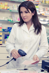 Female pharmacist checking prescription at counter in store