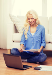 smiling woman with papers, laptop and calculator