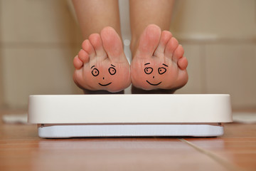 Feet on bathroom scale with hand drawn smiling cute faces