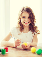 smiling little girl coloring eggs for easter