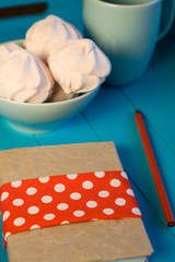 Delicate pink marshmallows in the blue plate, old notebook