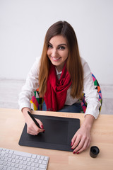 Smiling beautiful woman working on graphic tablet in office