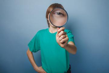 European-looking boy of ten years is looking through a magnifyin