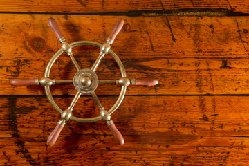 Brass Ship Wheel on Textured Wood