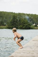 chłopiec skacze do wody