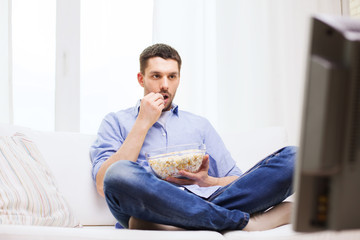 man watching tv and eating popcorn at home