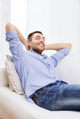 smiling man relaxing on couch at home