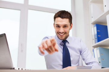 happy businessman pointing on you in office