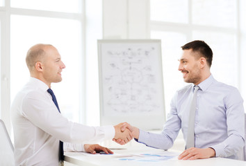 two smiling businessmen shaking hands in office