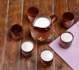 Clay jug and three cups of milk on a wooden table.