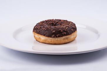 Chocolate glazed donut on white plate