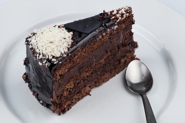 A slice of chocolate cake with chocolate glossy syrup topping an