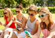 canvas print picture - smiling friends with smartphones sitting on grass