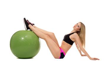Dreamy sporty girl threw her feet on fitness ball