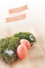 frohe ostern banderole und rote eier im moos