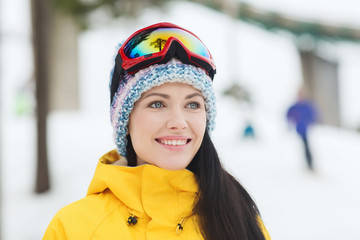 happy young woman in ski goggles outdoors