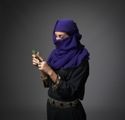 islamic woman messaging with phone