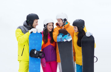 happy friends in helmets with snowboards talking