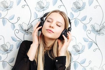 Young fashionable blonde woman enjoying music indoors
