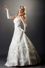 Lovely blonde posing in elegant wedding dress