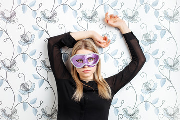 Young fashionable blonde woman posing in mask indoors