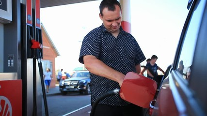 Young serious businessman refueling car tank at fuel station. HD