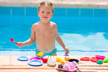 Toddler kid girl playing food toys in swimming pool
