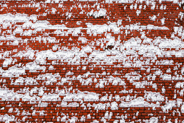 red brick wall covered with snow