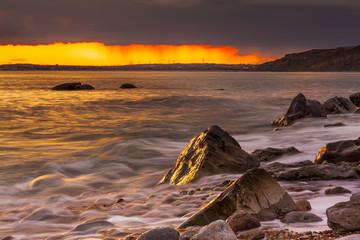 Rocks at Osmington Reflecting Sunset Colours