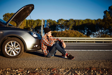 Young brutal man sits near car talking on cell phone
