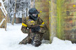 Experienced sportsman in professional paintball armor on winter
