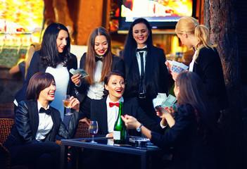 elegant fashionable women gambling in night club