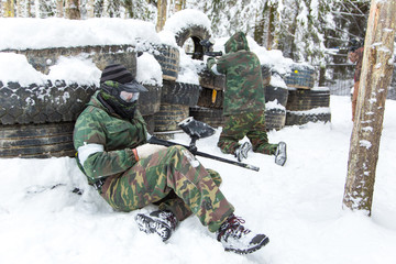 Two men defending tire paintball fortification covered with snow