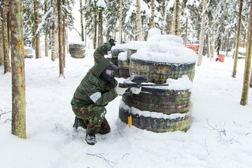 Two brothers defending tire paintball fortification covered with