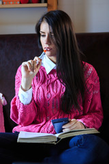 Attractive brunette woman student reading/ studying