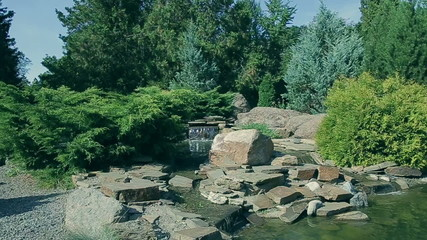 The landscaping flying camera over small lake and waterfall