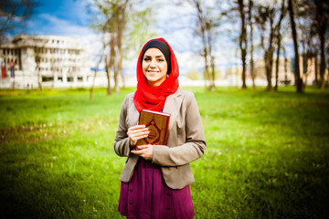 Muslim woman wearing hijab and holding a holy book Koran
