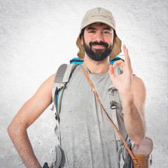 Backpacker making Ok sign over white background
