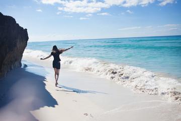 A young woman runs along the seacoast