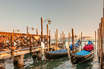Gondolas docked to the poles on the Grand Canal in Venice.