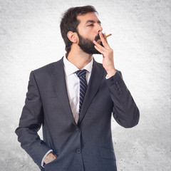 Businessman smoking over isolated white background